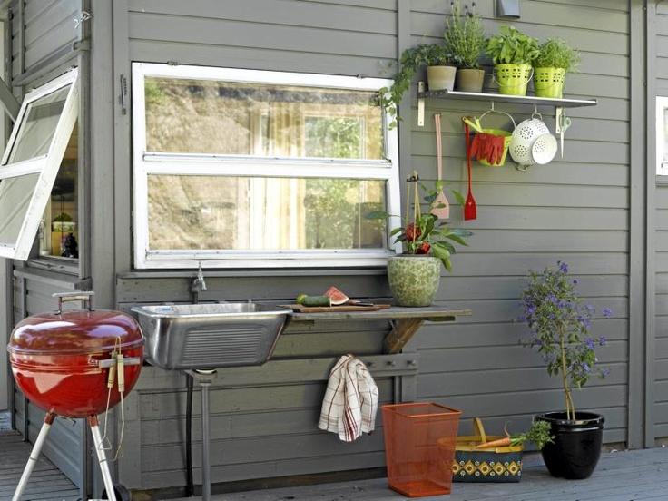 Det er deilig med et lite utekjøkken på sommerhytta. Her har grillen fått plass ved siden av vasken, hyllene brukes som benk og til oppbevaring av urter mens knaggene er praktiske for kjøkkenhåndklær og redskaper.