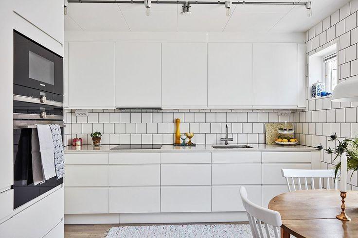Vitt traditionellt kakel och bänkskivor av Silestone kompositsten gör köket ljust och stilrent. Kökslucka Line med grepplist | Ballingslöv
