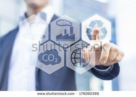 Businessman touching recyclable button for sustainable development with office buildings in background - stock photo