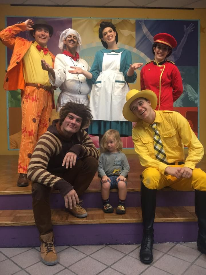 Young boy sitting in front center and surrounded by actors costumed for Curious George.