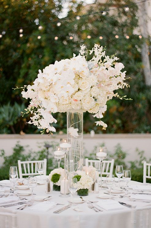 An Elegant centerpiece features orchids and roses surrounded by floating candles in staggering heights.