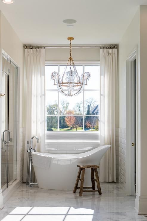... A Vintage Freestanding Bathtub Paired With A Polished Nickel Floor  Mount Tub Filler Sits In Front Of White Beveled Subway Backsplash Tiles And  Beside A ...