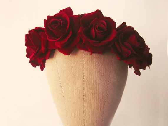 A striking red rose flower crown featuring luscious velvety roses on a handwoven, bark-covered headband. The deep burgundy colour is full of