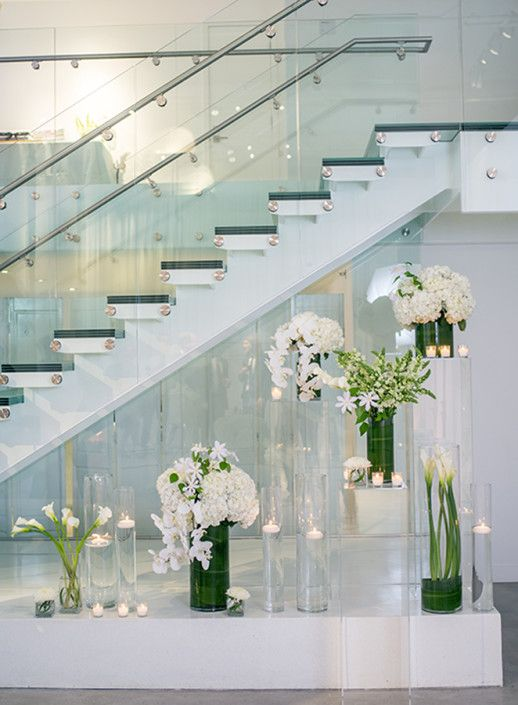 Photo Credit: Brian Stansfield. Modern wedding flower display under stairs at Chez Chicago. Wedding Décor at Chez. Long table setting. Chicago Wedding Venue. Chez. Chicago Wedding Loft. Wedding Inspiration. Contemporary Wedding. Wedding Decor. Wedding Ideas. Loft Wedding. Glass Staircase.