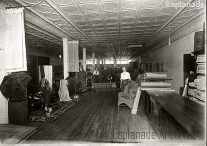 An interior view of the J.C. Beveridge Ltd. store in Medicine Hat, showing sales staff and customers in the textiles and linoleum department on the upper floor of the building (1913),