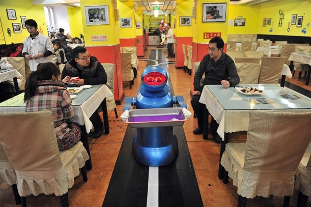 A robot that specializes in delivering food holds an empty tray after serving meals to customers at the Robot Restaurant in Harbin, China.