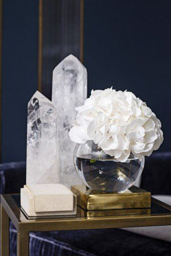 Consider your palette…k..The white hydrangea in a simple crystal bowl is perfect with the rock crystal oblisks for a monochromatic chicness.