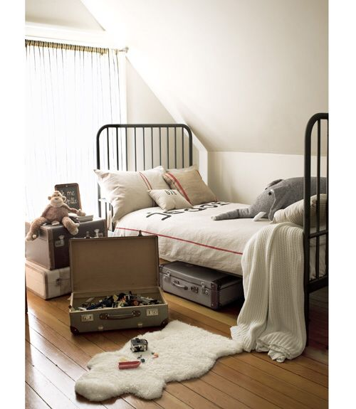 Cozy Bedroom  Linens by My Adobe Cottage adorn an Ikea bed in the boys' bedroom of this San Francisco home. Displayed in stacks or stored away behind closet doors, old trunks are the perfect size for organizing toys by type or likelihood of use.