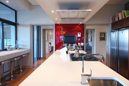 Walnut kitchen with red glass splash back and white caesar stone tops