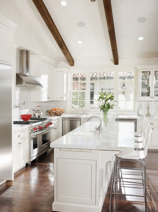 White kitchen with dark floors and high ceiling