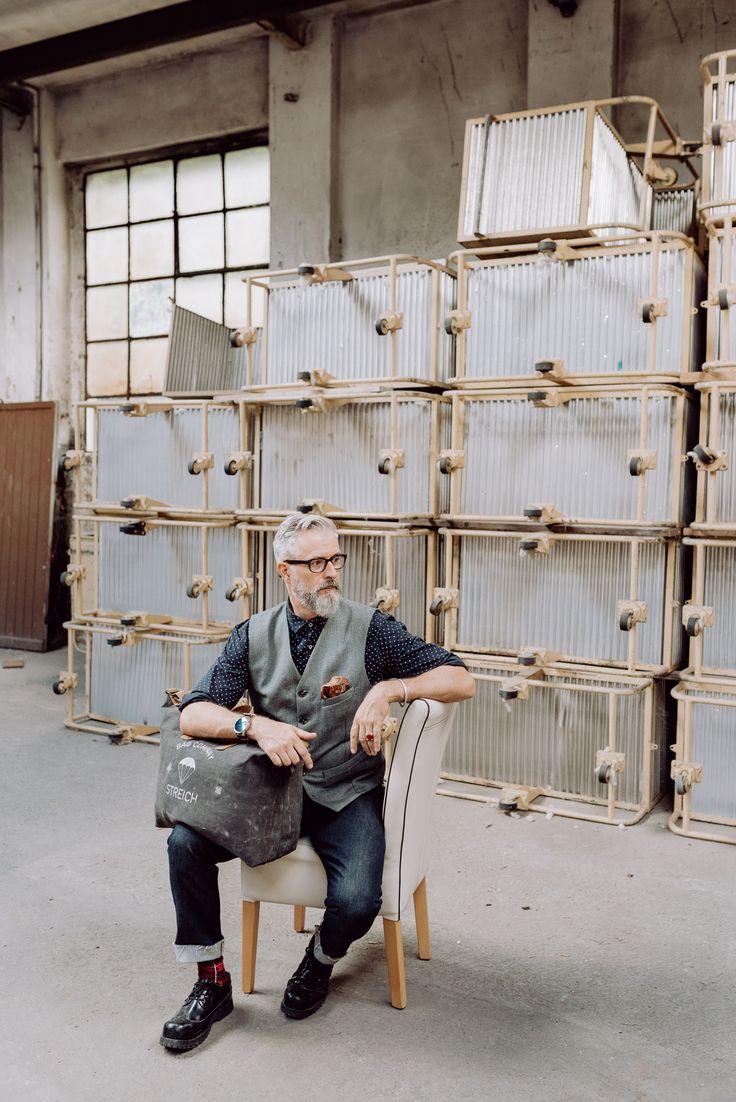 the designer bruno streich and his SOHO bag out of world war ll swiss army tent canvas and french army gunbelts. #streichbag #brunostreich #waistcoat #beard #beardmodel #saltandpepper #glasses #waistcoat #denim #selvedgedenim