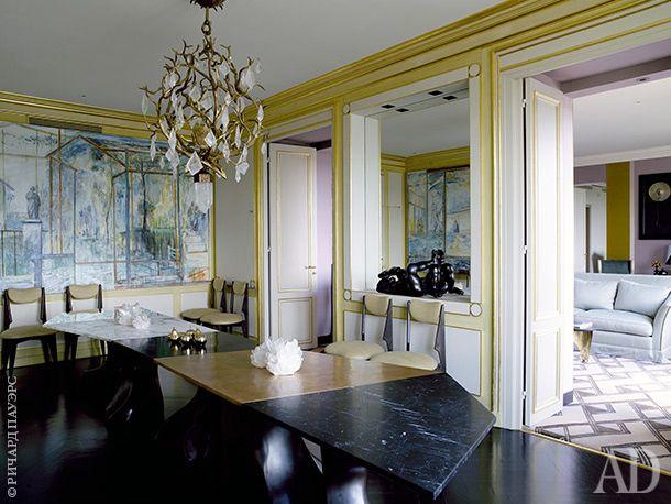 На потолке столовой красуется скульптурная люстра работы Эрве ван дер Стратена. Стол издвух видов мрамора (черного ибелого) и бронзы создан по дизайну Эрика Шмитта. На стене — картины Валерия Кошлякова, которые он написал специально для этой квартиры. В зеркальной нише — скульптура Жозефа Ривьера L'Homme Au Soleil. Сквозь дверной проем видна малая гостиная с диванами отLeinis.