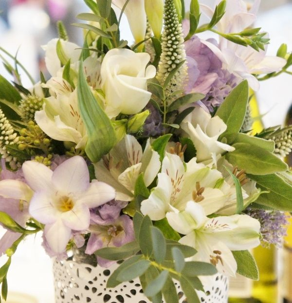 White and lavender wedding table-centre of freesia, lisianthus, veronica, alstroemeria, statice, trachelium, eryngium thistle and berried ivy. Florissimo, Shropshire