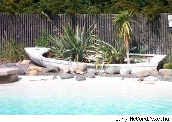 DIY Backyard Landscaping | Pool-side landscape incorporating an old row boat, source: sxc.hu.