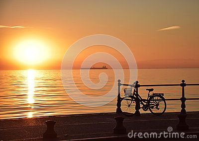 Sunset in Thessaloniki by the seafront with a bike left on the railings. Walking Thessaloniki app, Route 03 - St Sofia