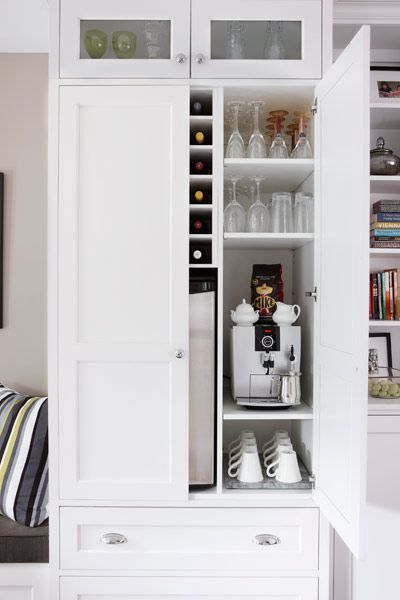 A coffee and wine bar is tucked into one of the pantry units; small glass-panel doors up top help lighten the look of tall cabinetry. | Photo: Stacey Brandford | thisoldhouse.com