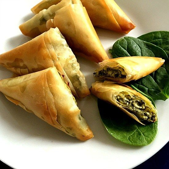 Greek spinach and cheese triangles or Spanakopita, a delicious snack or starter that will impress everyone having a bite.
