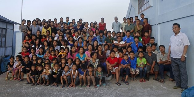 """Family members of Ziona (R) poses for group photograph outside their residence in Baktawng village in the northeastern Indian state of Mizoram, October 7, 2011. Ziona is the head of a religious sect called """"Chana,"""" which allows polygamy and was founded by his father Chana in 1942. Ziona has 39 wives, 94 children and 33 grandchildren. He lives in his 4 storey 100-room house with 181 members of his family. The world's population will reach seven billion on 31 October 2011, according to…"""