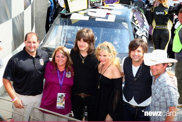 """Troy Alabama Fire Lieutenant Curtiss Shaver, winner of Crown Royal's """"Your Hero's Name Here"""" program, presents the trophy with wife Cindi and Reid Perry, Kimberly Perry and Neil Perry of The Band Perry and Justin Moore after winning the NASCAR Sprint Cup Series Crown Royal presents the Curtiss Shaver 400 at the Brickyard at the Indianapolis Motor Speedway on July 28, 2012 in Indianapolis, Indiana."""
