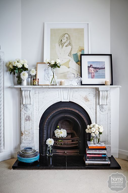 stacked books, flowers and ases on the hearth of a fireplace