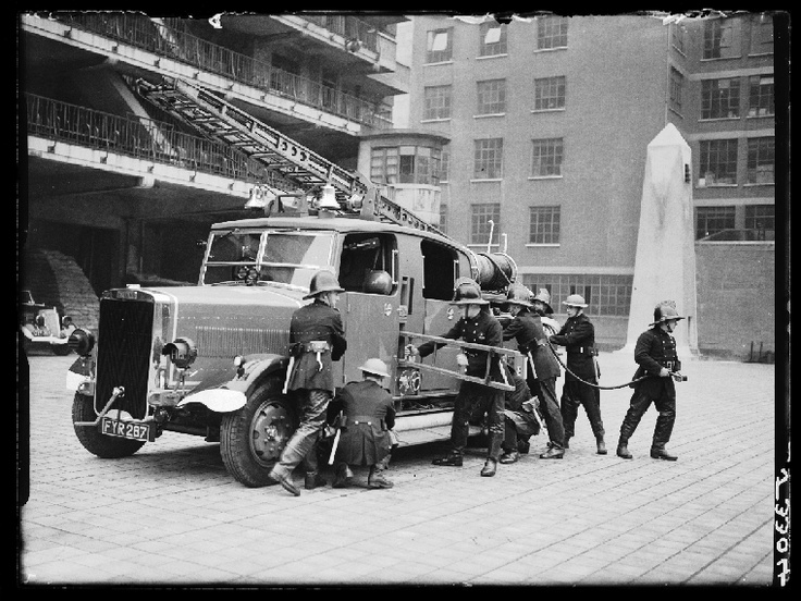 A photograph of fire fighters operating a new fire engine, taken in July 1940 by Tovey for the Daily Herald.    This fire crew are unloading hoses and a ladder from a new fire engine. The fire services in London were severely tested during the second world war. The Blitz, the German aerial bombing campaign of the capital, began in the late summer of 1940 and saw widespread devastation all over London.