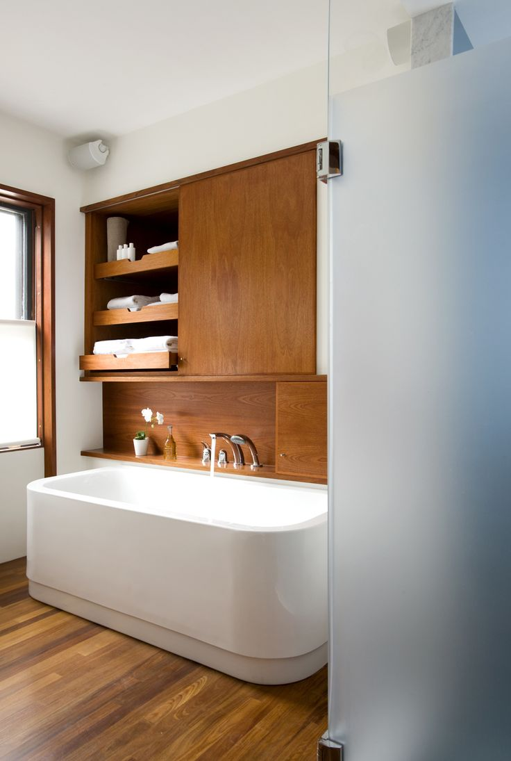 """The leftmost cabinet above the Duravit bathtub (equipped with KWC fixtures) occupies the space where a doorway once lead into the living room, creating unnecessary traffic from the home's public spaces through to the master bedroom.The new bathroom features a minimal palette of white and teak. """"It's able to hold up on boat decks so is good for a bathroom,"""" Klug says. It also makes the heated floor that much nicer to walk on in the morning.  Photo by   Eric Roth"""