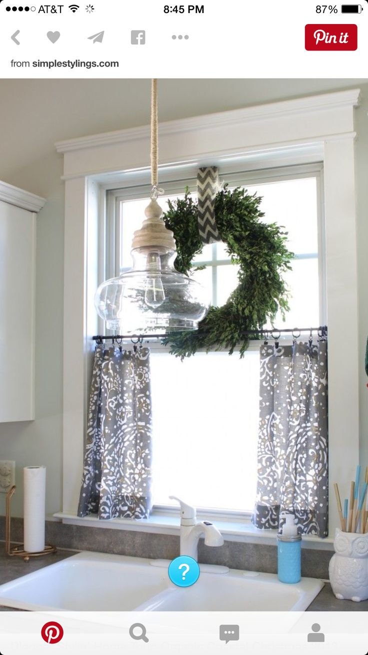 cute cafe rod...ring clipped curtains for bottom half, wreath above by way of white tension rod. Install removable shelf at halfway point. Use antique white farm light/remount over sink. More