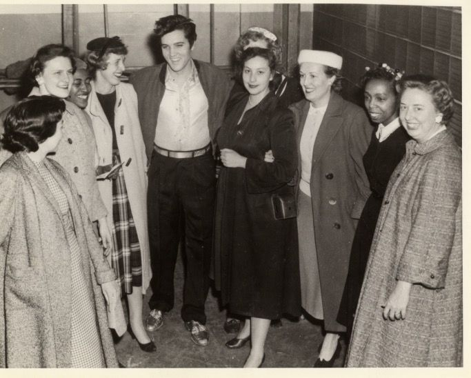 """View of singer Elvis Presley posing with members of the Women's Division of the Detroit Police Department at Olympia Stadium in Detroit, Michigan. Handwritten on back: """"Elvis Presley, Olympia Stadium, Detroit, 31 Mar 1957 with members of the Detroit Police Dept.'s Womens Division. Lucia Simpson? Marion Moore. Marge Wesley."""""""