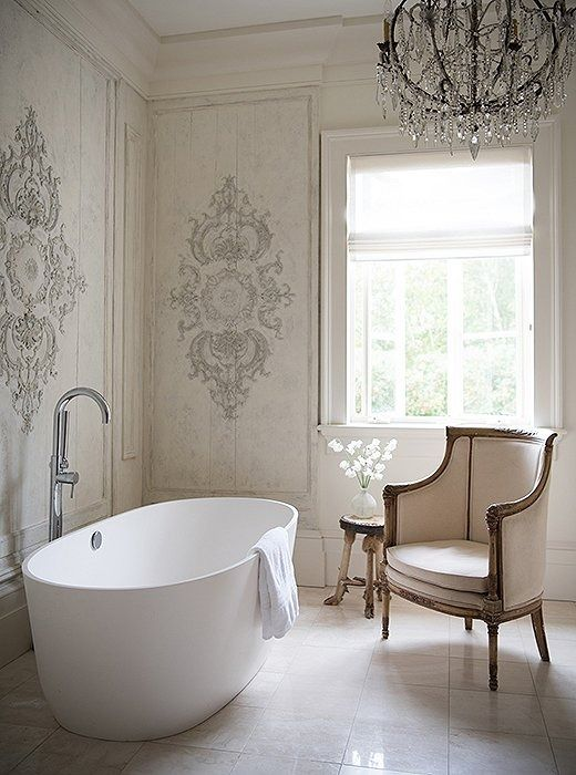 In this glam bathroom, the modern bathtub stands out almost as a piece of art amongst wall paneling salvaged from the South of France.