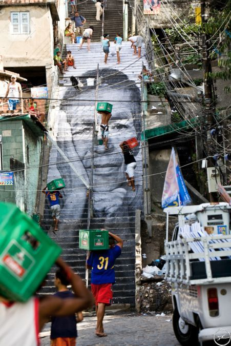Women Are Heroes, une exposition de rue de l'artiste français JR, dans le bidonville Moro de Providencia, à Rio de Janeiro, en 2008. En hommage aux femmes, qui jouent un rôle essentiel dans la société mais sont les premières victimes des guerres et des violences, l'artiste a tapissé les façades de maisons et les rues d'immenses photos des femmes de la favela