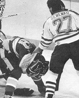 Kings' Rick Lapointe turtles under imminent threat of a Dave Semenko punch.