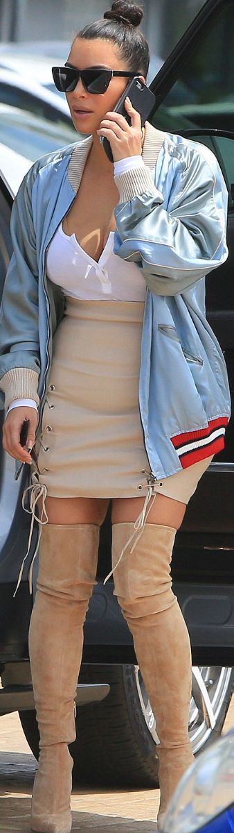 Who made  Kim Kardashian's black sunglasses, suede thigh boots, blue jacket, and tan lace up skirt?