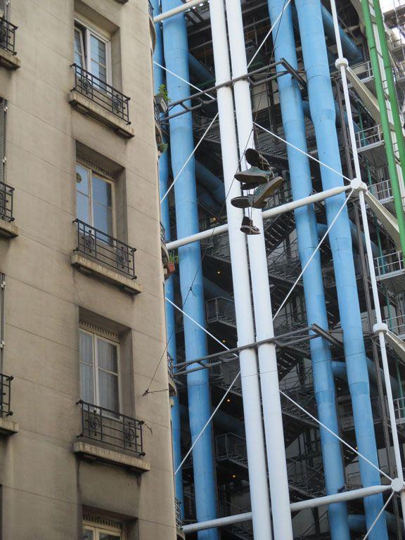 los zapatos colgando y atrás el Pompidou en Paris