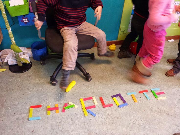 Kinderen leggen de letters van hun eigen naam met lollystokjes