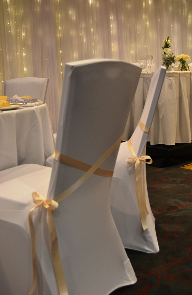 White lycra chair covers with peach satin ties. Styled by Greenstone Events.