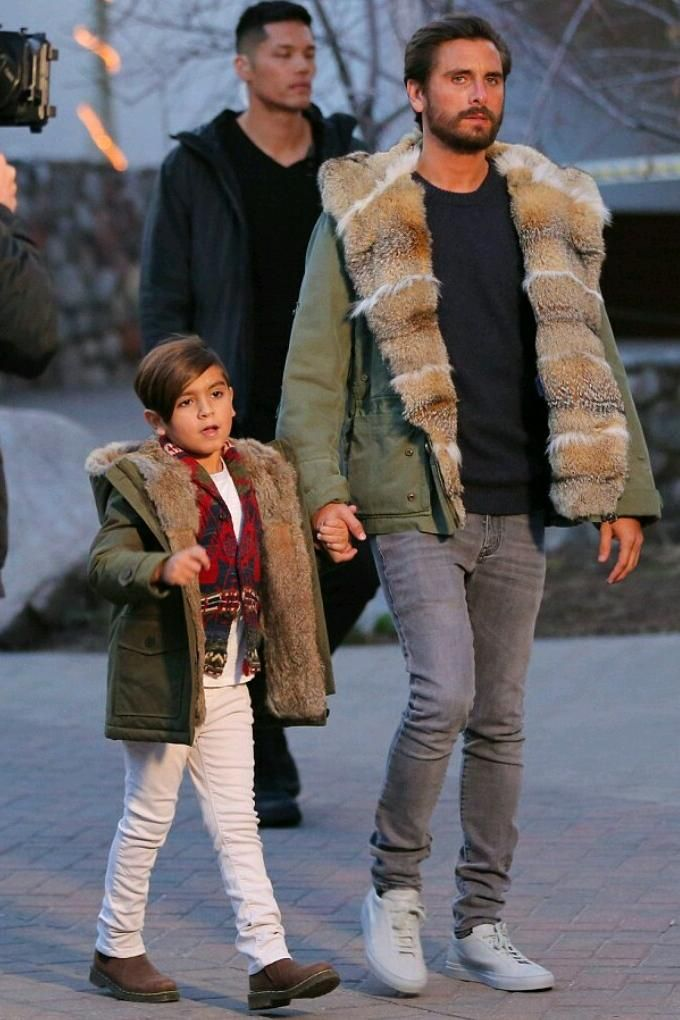 Scott Disick wearing Saint Laurent Original Low Waisted Skinny Jean in Washed Grey Stretch Denim, Common Projects Original Low Sneakers and Ermanno Scervino Army Green Fur Hooded Jacket