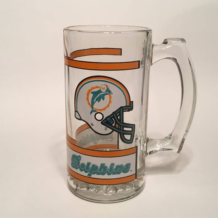 The Miami Dolphins are the only team in the history of the NFL to put a perfect season on the scoreboard. From the first game though Superbowl VII, the 1972 Dolphins remained unconquered, thereby securing their place in football history.  This glass would make a wonderful gift for a Miami Dolphins fan, or a great addition to any NFL memorabilia collection.  This sturdy vintage (mid 1990s) Dolphins glass measures 5 1/2 inches high and about 3 inches across at the mouth. It is in excellent...