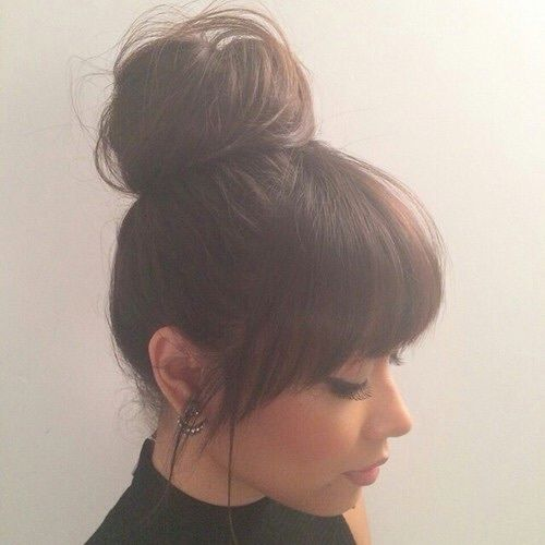Thick, Full, Angled, Face Framing Straight Bangs With Big Messy Bun Styled As A Mix Of The Top Knot & Sock Bun
