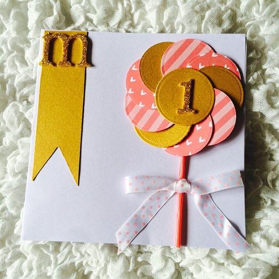 Biglietto di auguri per primo compleanno con iniziale e girandola realizzato in cartoncino e glitter oro e rosa. Invito, partecipazione.