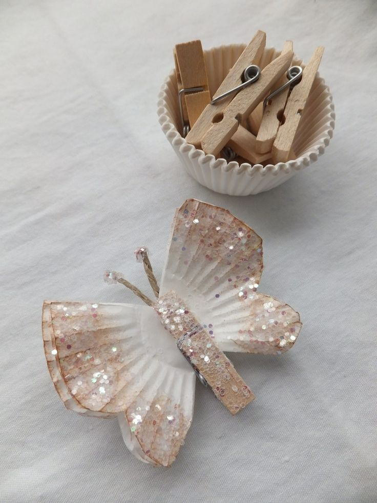 DIY butterfly decorations using cupcake wrappers and miniature clothespins.