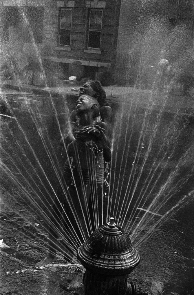 Leonard Freed The fire hydrants are opened during the summer heat, Harlem USA, NY, 1963. From Magnum Photos
