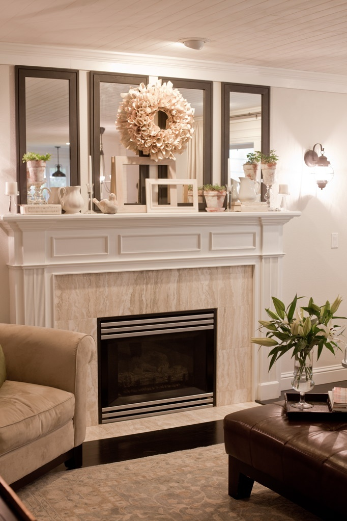fireplace mantle - love the 4 vertical mirrors!!  Need to repaint my mantle and change the face plate