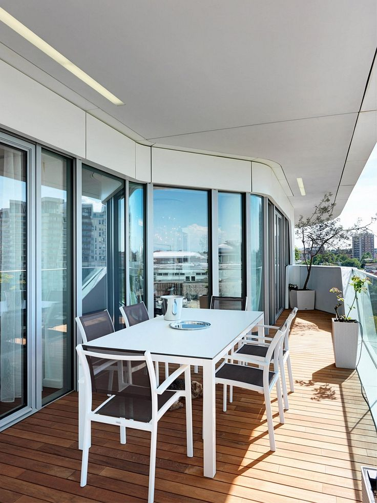 Apartments:Outdoor Dining Space In Balcony With Dining Sets With Sleek Dining Table And Dining Chairs Also Glass Windows Also Plants In Pots Also Laminate Floor With Enjoying The View Outside Modern Interior Design of Luxury Apartment in Milan To Inspire You