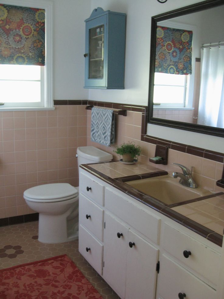 50s bathroom, peach tile with reddish-brown trim. Blue and coral  accessories.