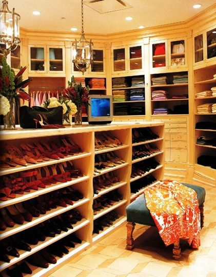 This grandeur closet-room has maximized space with floor-to-ceiling drawers, shelves, and cupboards; and a long central shelving unit for shoes