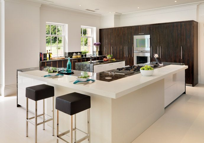 Sharp geometric lines, as used for this L-shaped island, create a contemporary look and feel. Here walnut veneer has been used for a warm natural finish and contrasts with the high-gloss and matt white finishes of the two islands. Davonport Linear kitchen, made in Colchester. Kitchens from £35,000. davonport.com #utopiamag #modernbritish #kitchen
