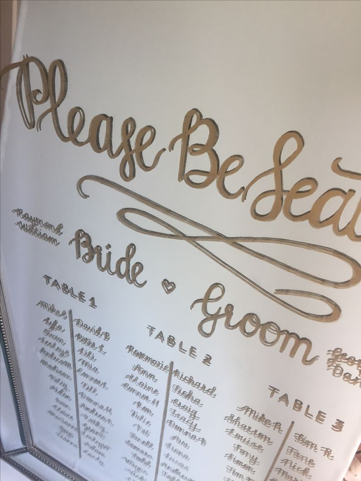Gold calligraphy wedding seating plan on an antique mirror