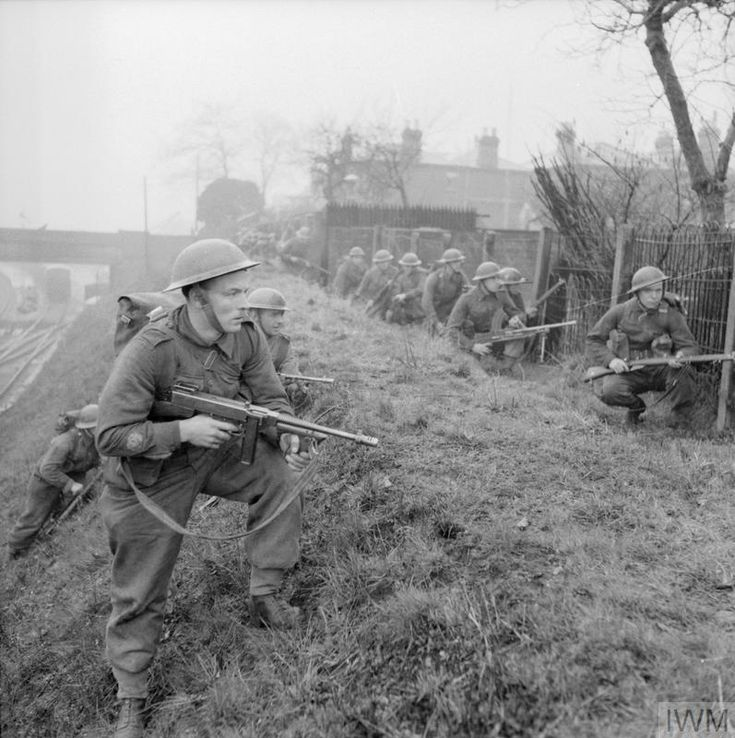 Infantry training at 47th Division School of Battle Drill at Lymington near Southampton, 11 March 1942. The troops are seen advancing between the backs of houses and a railway line.