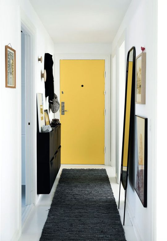 Sunshine yellow door, white walls, leaning mirror, shallow wall-mounting storage, framed pics, textured rug
