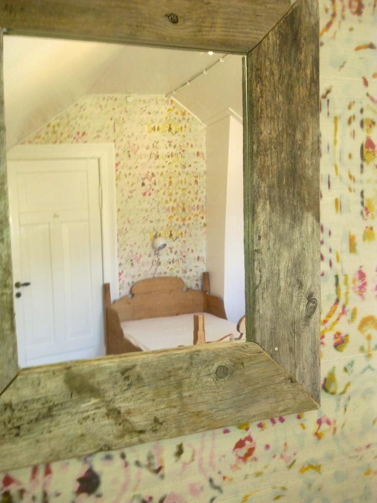 Bikuben - soverommet på hytten med de mange sengeplassene nå med nytt tapet. Speilet er laget av rekved i fjæren.